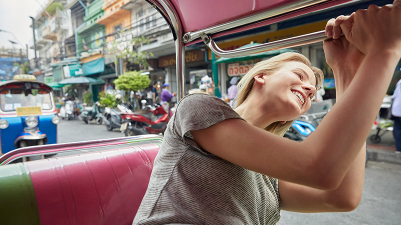 Woman sticking her head out a car window and smiling.